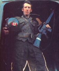A soldier holding a gun and a helmet with a Canadian flag decal